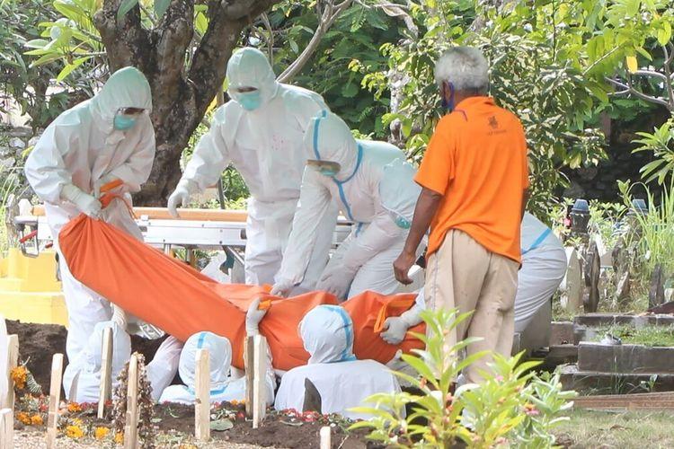 Pemakaman pasien Covid-19 yang meninggal dunia setelah dirawat di RSUD Kota Mataram. Petugas melakukan pemakaman sesuai pemakaman protokol Covid-19, Rabu (10/2/2021) sore, di Pemakaman Umum Karang Medain, Kota Mataram. (Fitri R/Kompas)