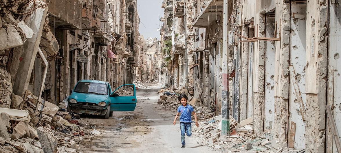 Seorang anak berlari di jalan yang dipenuhi reruntuhan. Bangunan-bangunan tampak rusak parah akibat perang di Libia. (UN News)