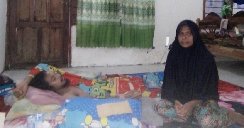 Rohana bersama anaknya yang terbaring karena trauma dan kelelahan karena banjir. (Ntb News/Nur Hasanah)
