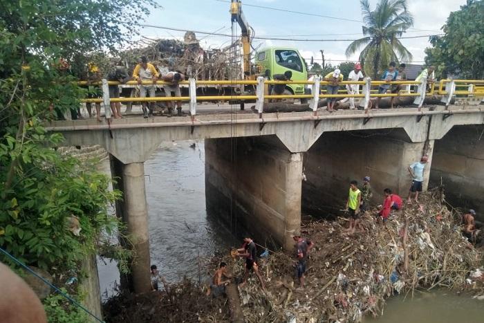 Warga dan petugas gabungan membersihkan sampah di jembatan Desa Sondosia. (Ntb News/Arif Sofyandi)