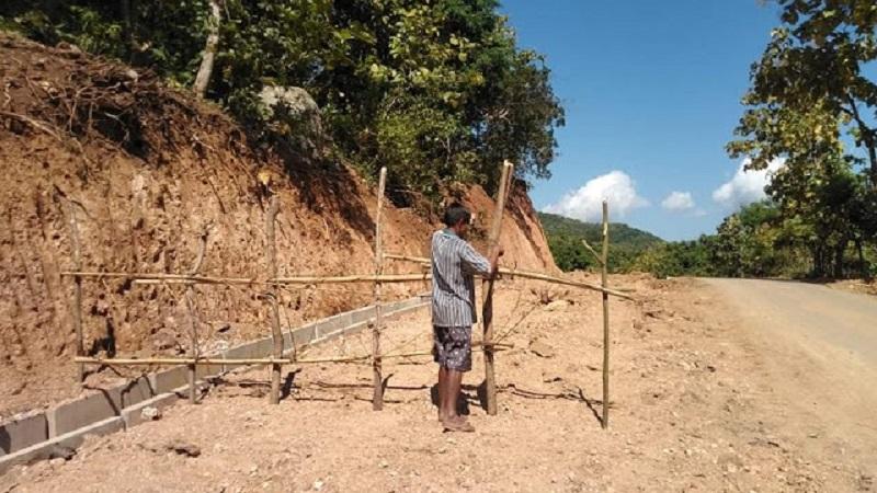 Seorang warga memblokir proyek pelebaran jalan di Desa Waworada. (Istimewa)