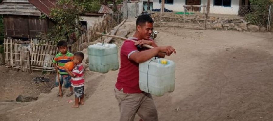 Salah seorang warga Toke, Desa Kala, Kecamatan Donggo, Kabupaten Bima sedang memikul air. (katada.id)