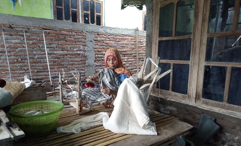 Kamusiah saat mengurai benang (moro) menggunakan janta dan langgiri (Ikbal Hidayat/Ntb News).